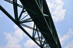 44 upward view of steel bridge gurders against a blue sky.