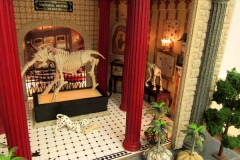 45b detail of miniature room sculpture of museum room with tiled floor displaying animal skeletons.