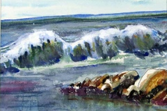 71 rolling wave crashing on seaside rocks.