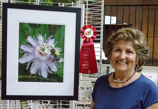 Shirley Brutko nect to her photo of flower and bee
