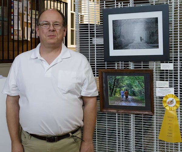 Norman Stringer in front of his photo of child in the woods