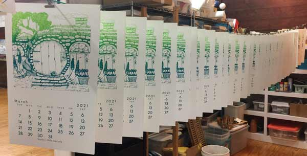 row of March 2021 silk screened calendar pages hanging up tp dry in the Southern Arts Society's studio.