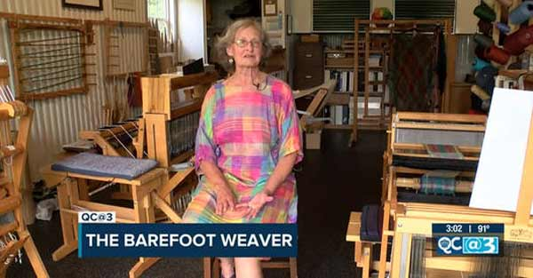 Sue Helmken, while barefoot, site in front of her looms for WBTV interview titled The Barefoot Weaver.