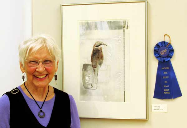 Artist Anne Cowie in front of her first place artwork at Southern Arts Society's Nature Reconsidered 2021 art exhibit.