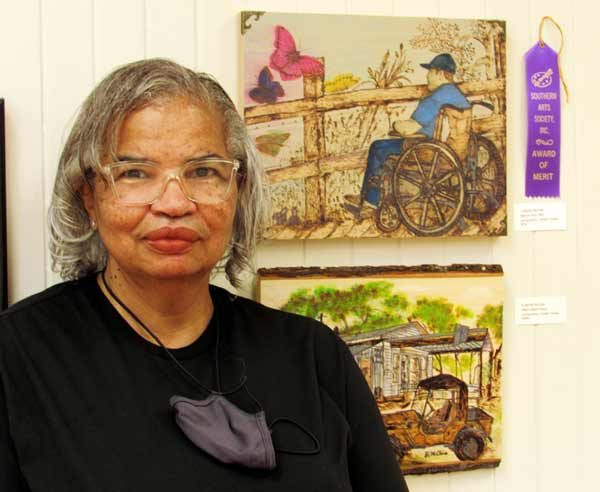 Artist Bertie McClain in front of her merit award-winning artwork at Southern Arts Society's Nature Reconsidered 2021 art exhibit.
