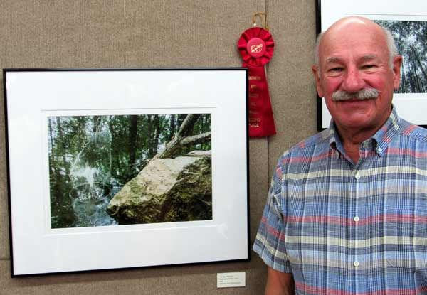 Photographer Alex Pietersen in front of his second place-winning photography at Southern Arts Society's Trail 2021 art exhibit.