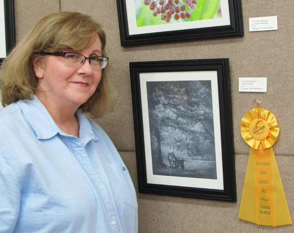 Photographer Ellen Devenny in front of her third place-winning photography at Southern Arts Society's Trail 2021 art exhibit.